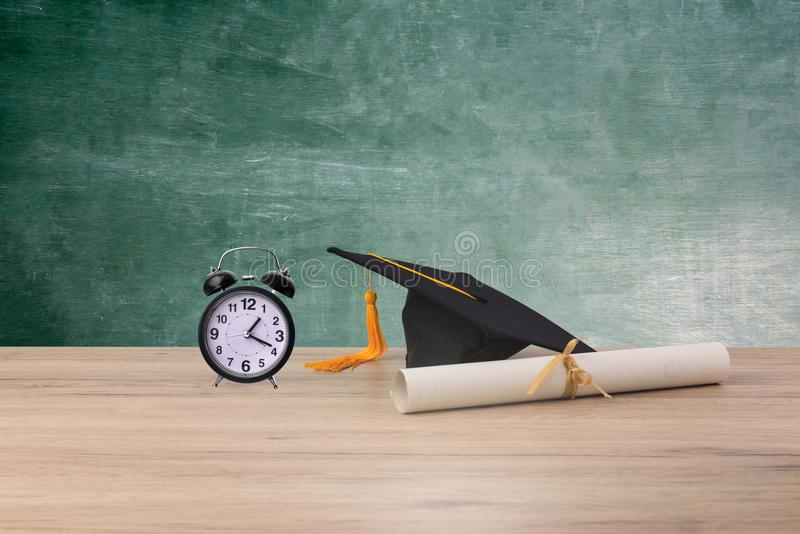 Black graduated cap. Degree Certificate and Alarm clock pace on wood background stock photos