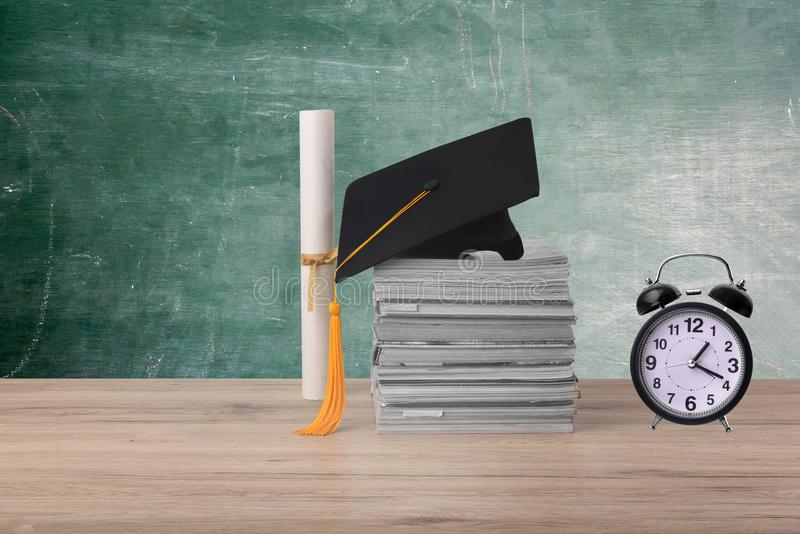 Black graduated cap. Degree Certificate and Alarm clock pace on wood background stock images