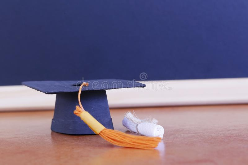Black graduation cap, diploma in classroom. graduate certificat. E program, Education Insight Concept stock photography