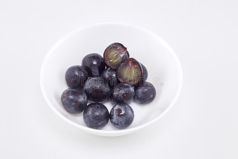 Black grape in bowl on white. Fresh Black grape in bowl on white background Sunshine at noon With empty space available for Text design stock photos