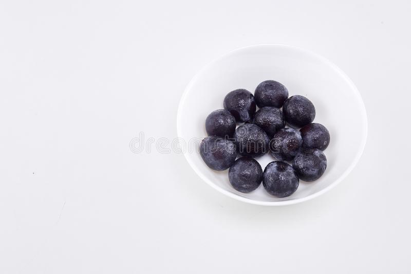 Black grape in bowl on white. Fresh Black grape in bowl on white background Sunshine at noon With empty space available for Text design stock image