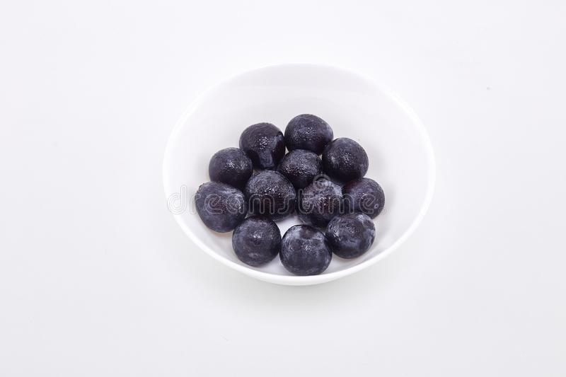 Black grape in bowl on white. Fresh Black grape in bowl on white background Sunshine at noon With empty space available for Text design stock photo