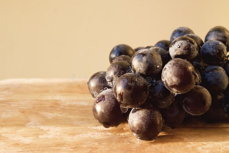 Black grape in wooden tray with water drop and sunlight. Fruit background. stock photography