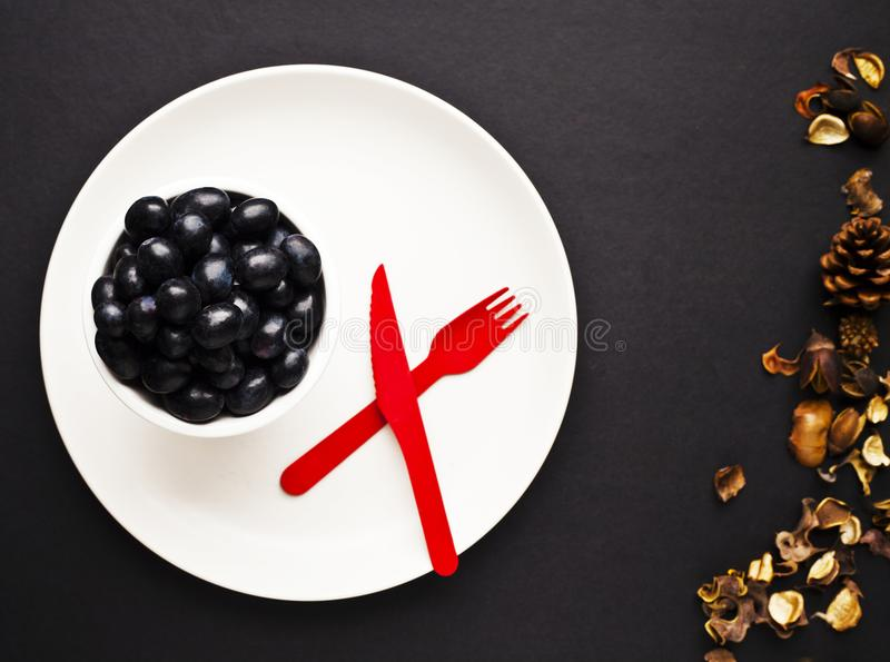 Black Grapes on white plate with red knife and folk stock images