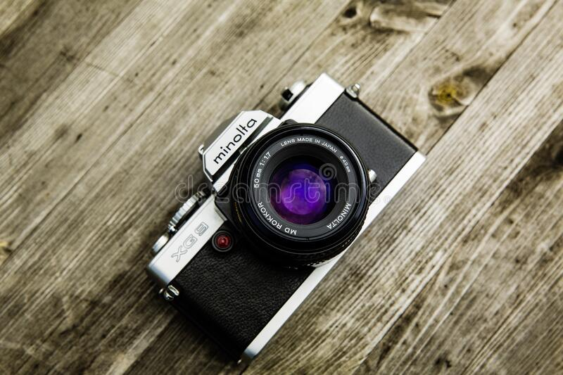 Black and Gray Minolta Dslr Camera on Top of Brown Wooden Surface royalty free stock photography