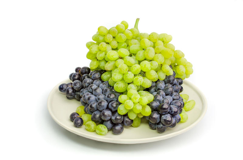 Black and green grapes bunches on white plate isolated on white royalty free stock photography