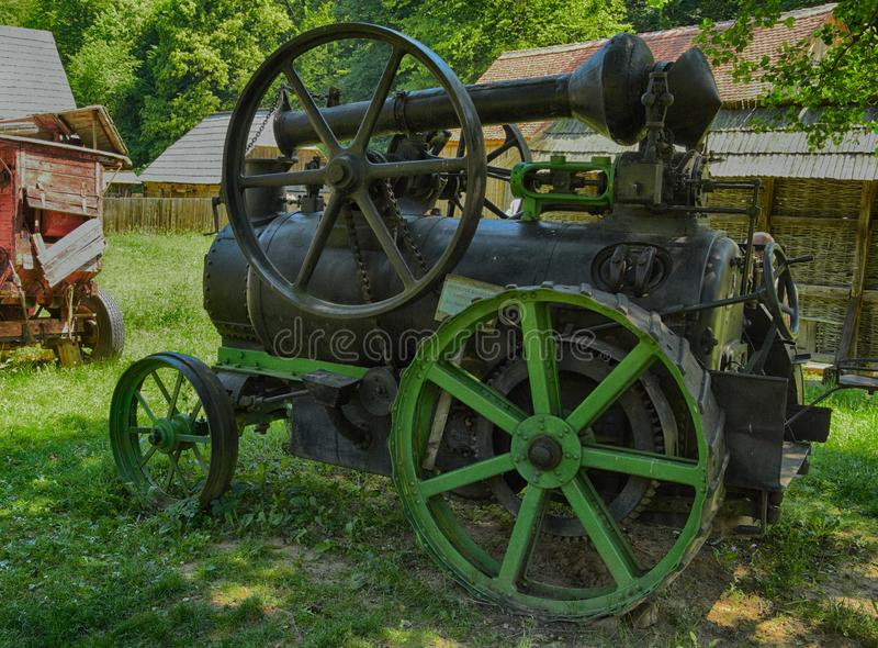 Old farm machinery. Black and green old farm machine use in agricultures for working land stock photo