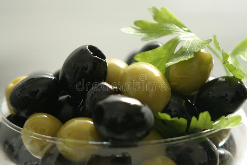 Black and green olives. In a transparent vase with greens royalty free stock photo