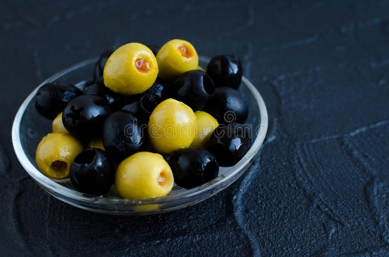 Black and green olives. In glass bowl on dark stone background. Copy space stock photos