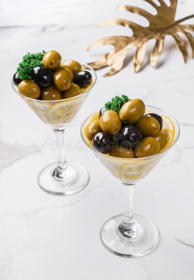 Black and green olives in glass on white marble background. Various kinds of Mediterranean pickled olives. Top view.  royalty free stock photo