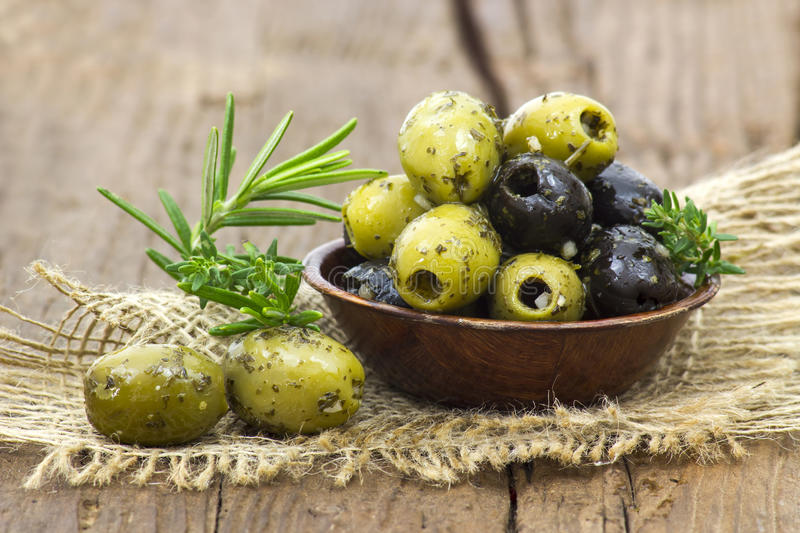 Black and green olives marinated with garlic and fresh mediterra stock photos