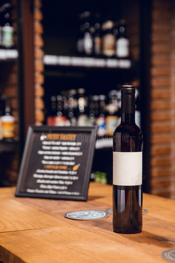 Black and green wine bottle with black and white label and cap in wine shop stock image