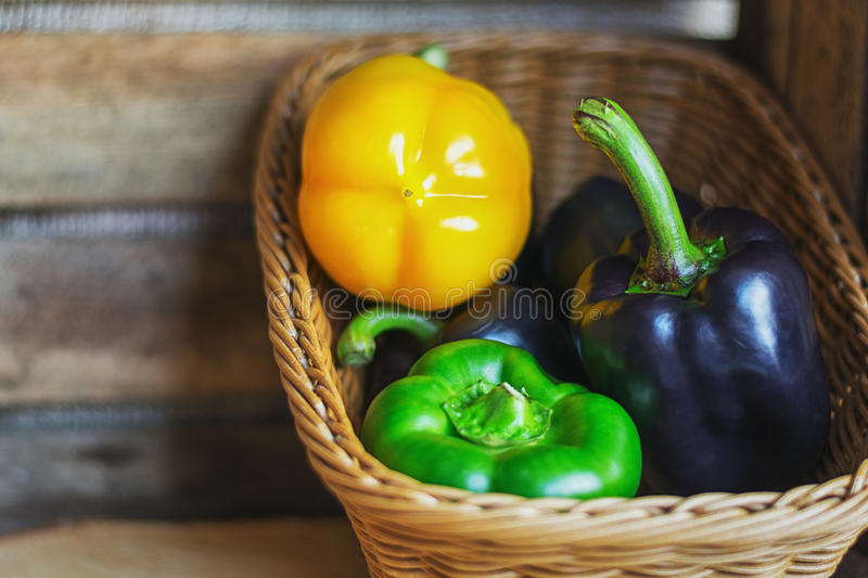 Black, green and yellow paprika`s in a basket. royalty free stock photo