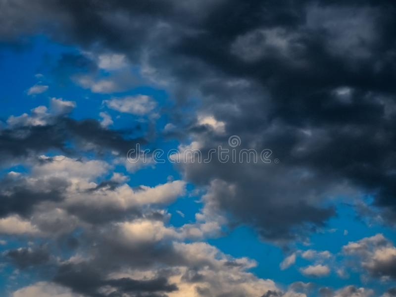 BlAck and grey clouds in summer storm. White, sky, blue, dark, afternoon, dramatic, atmosphere, rain, outdoor, infinity, univers, space stock photo