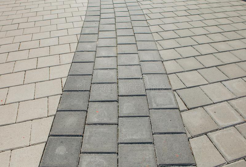 Black and grey cobblestones of a footpath have been laid in a geometrical pattern. They are worn with time royalty free stock images