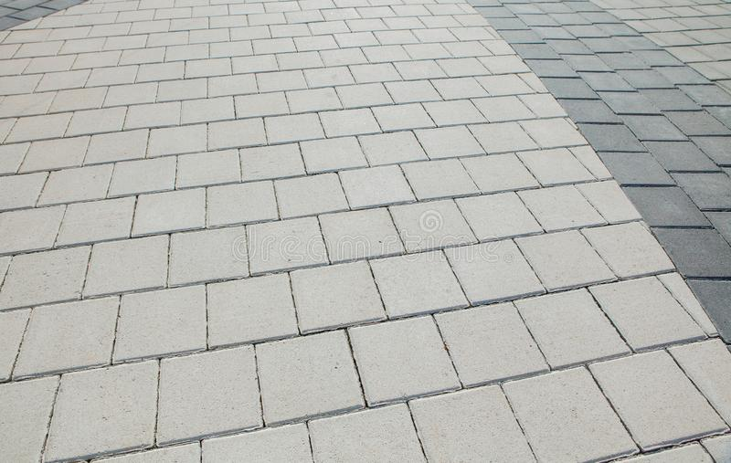 Black and grey cobblestones of a footpath have been laid in a geometrical pattern. They are worn with time stock images