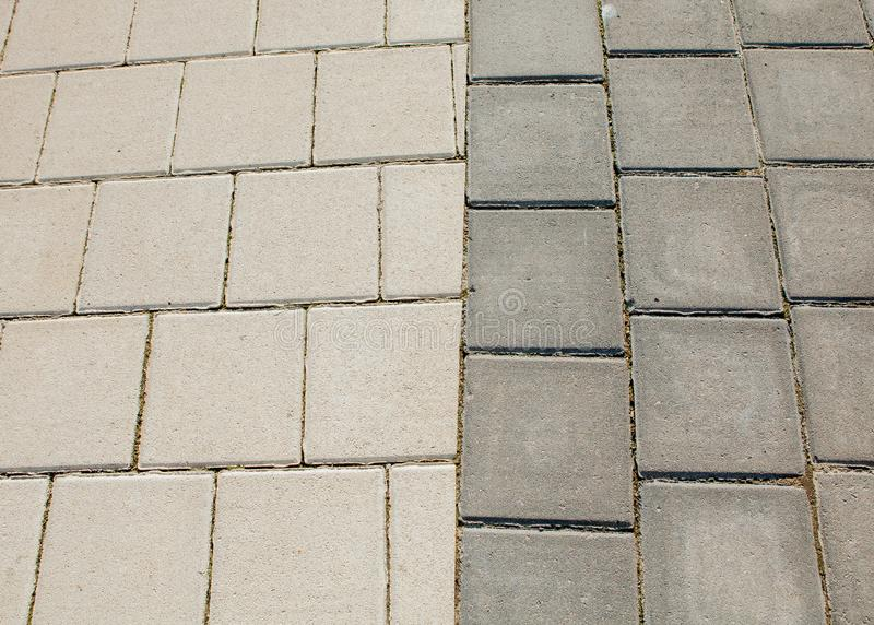 Black and grey cobblestones of a footpath have been laid in a geometrical pattern. They are worn with time stock photos