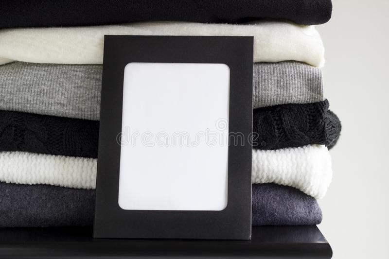 Close-up blank frame and stack of folded clothes on white background wall. Black, grey and white textiles. Copy space for text. Monochrome concept royalty free stock photos