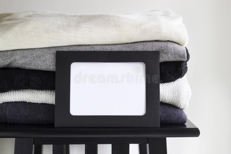 Close-up blank frame and stack of folded clothes on white background wall. Black, grey and white textiles. Copy space for text. Monochrome concept stock image
