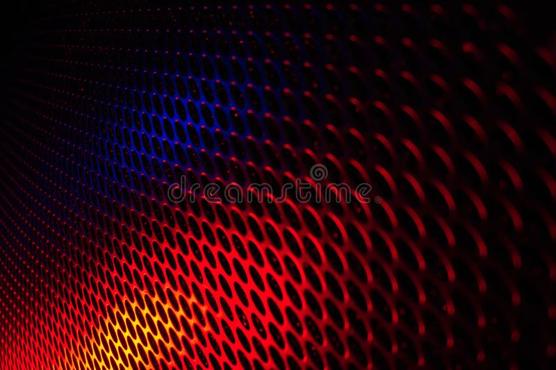 Black grid speaker texture with red and blue colors. Front view royalty free stock image