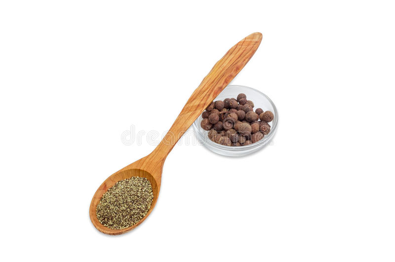 Black ground pepper in wooden spoon and allspice in bowl royalty free stock images