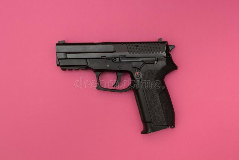 Black gun on a pink background stock photos