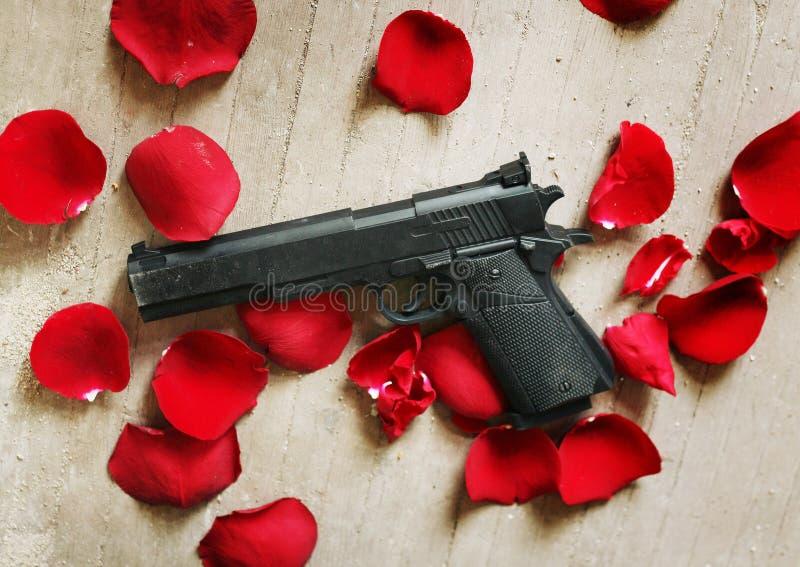 Black gun red roses petals stock images