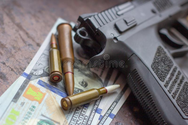 Black gun and weapon bullets on American dollars background. Military industry, war, global arms trade and crime concept.  stock image