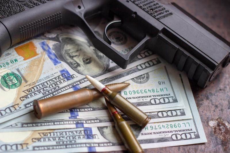 Black gun and weapon bullets on American dollars background. Military industry, war, global arms trade and crime concept. Black gun and weapon bullets on royalty free stock image
