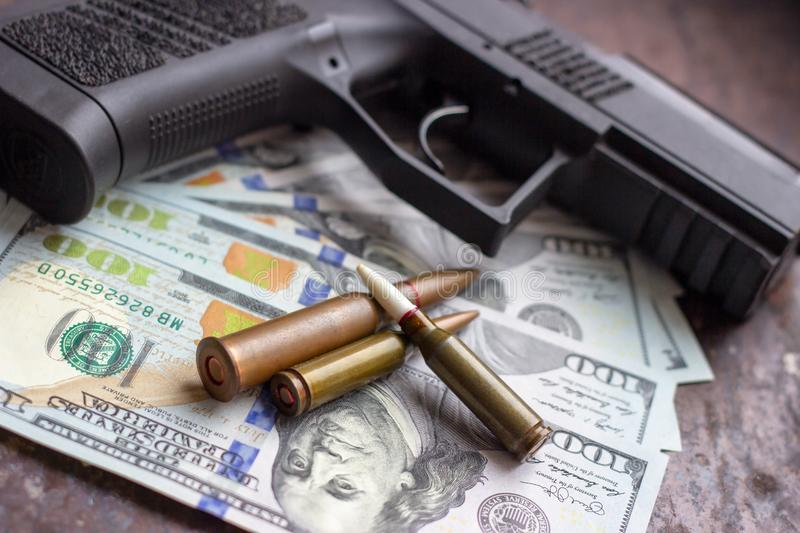 Black gun and weapon bullets on USA dollars background. Military industry, war, global arms trade and crime concept. Black gun and weapon bullets on American royalty free stock image