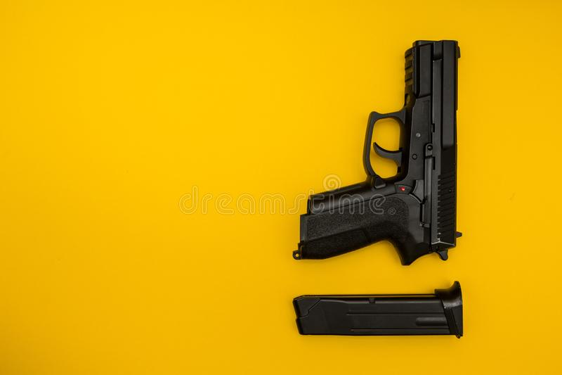 Black gun on a yellow background stock images