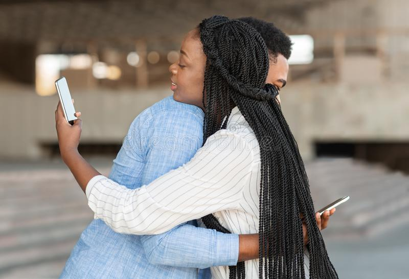 Black guy and girl hugging but looking at smartphones over shoulder. Smartphone addiction concept. Young men and women hugging each other, but looking at mobile stock photography