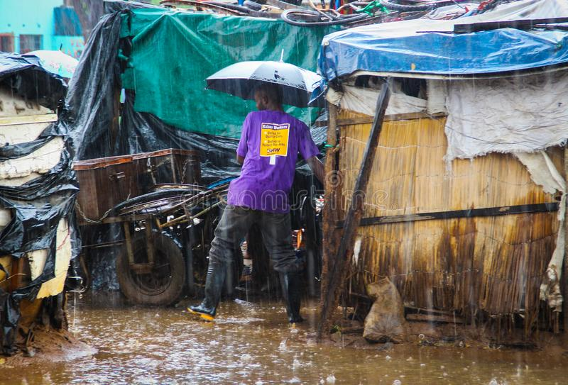 A black guy in rubber boots under an umbrella is pushing a cart in the pouring rain in the rainy season stock images