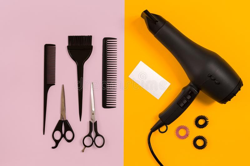 Black hair dryer, comb and scissors on pink and yellow paper background. Top view. Copy space. Still life. Mock-up. Flat lay stock photos