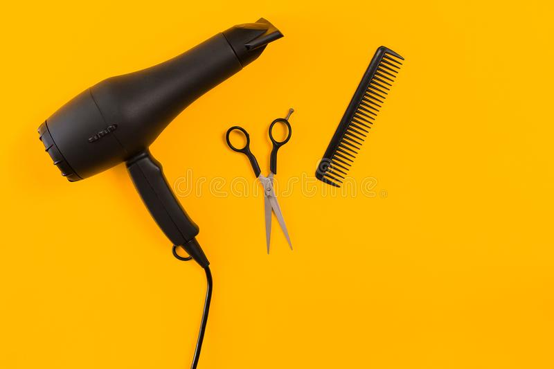 Black hair dryer, comb and scissors on yellow paper background. Top view. Copy space. Still life. Mock-up. Flat lay royalty free stock photo