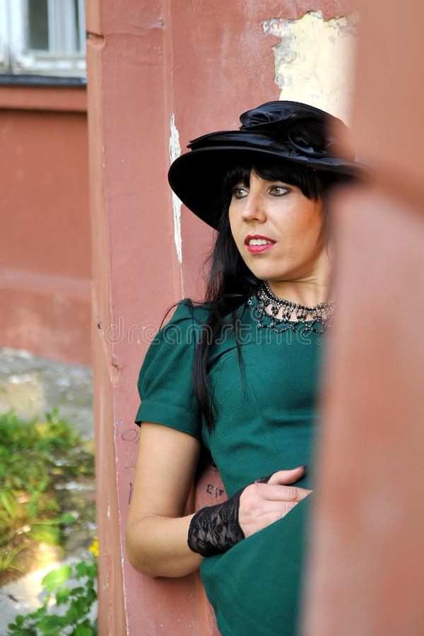 Black hair women on green dress with black hat royalty free stock image