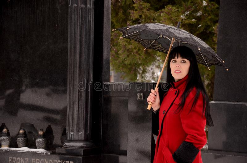 Black hair women on cemetery with umbrella stock image