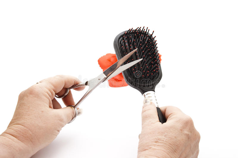 Black Hairbrush in hand with Scissors royalty free stock images