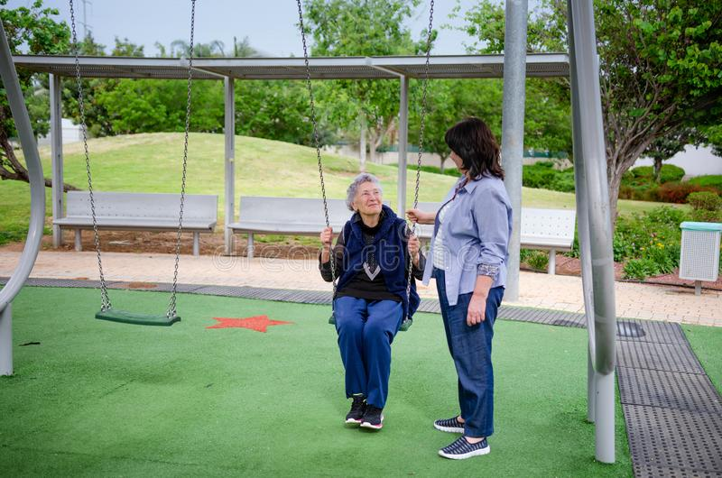 Senior adult woman enjoys swinging in the playground while carer protecting her. Black haired caregiver assists elderly women swinging on a swing set. Caring for stock photography