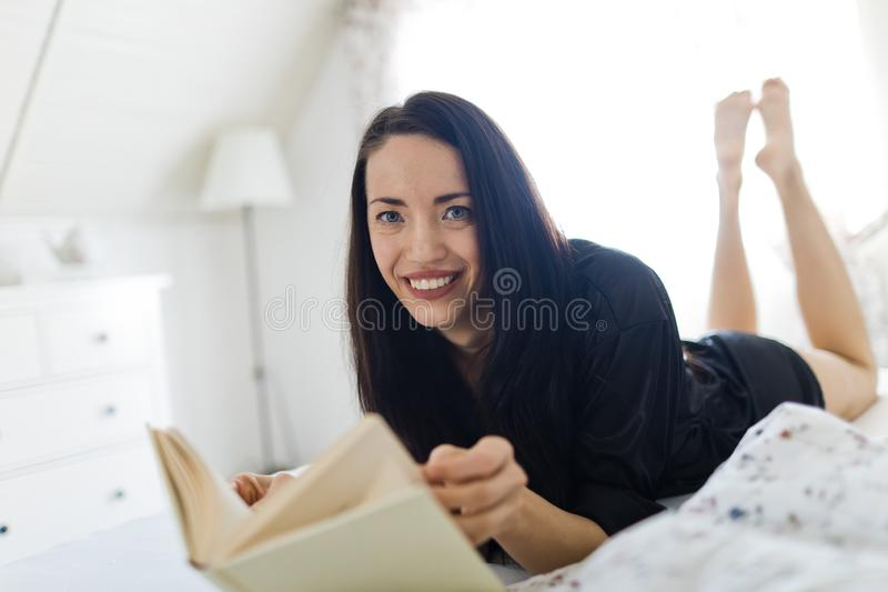 Black haired woman sleepwear laying on bed stock photo