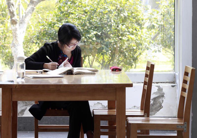 Black-haired woman studying in the library royalty free stock image