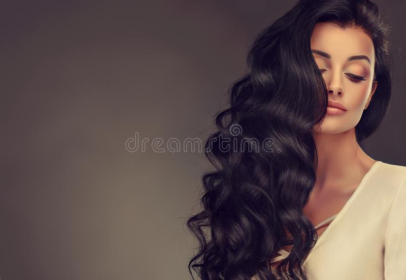 Black haired woman with voluminous, shiny and curly hairstyle.Frizzy hair. Young black haired woman with voluminous, shiny and wavy hair . Beautiful model with stock images
