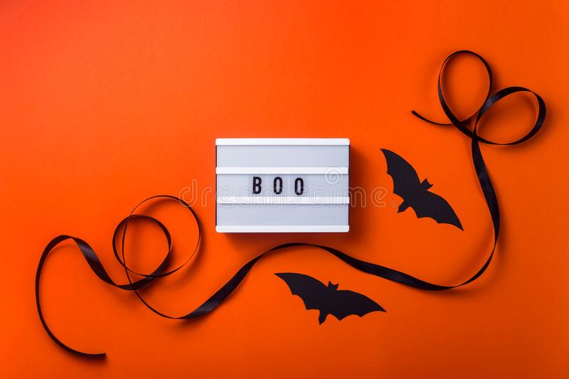 Black halloween characters and accessories on a bright orange background. Boo is written on a white panel among accessories for a Halloween party of a black stock images
