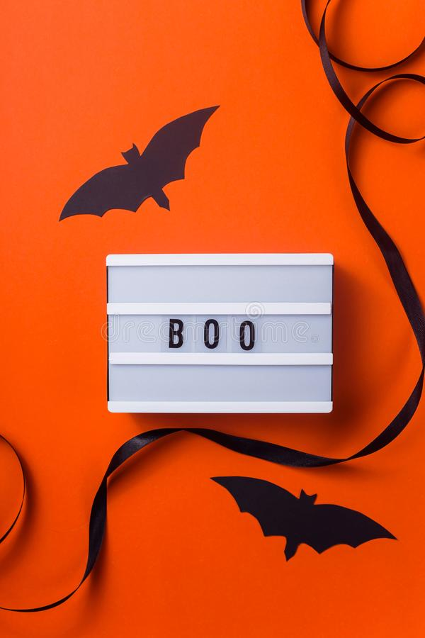 Black halloween characters and accessories on a bright orange background. Boo is written on a white panel among accessories for a Halloween party of a black stock photos