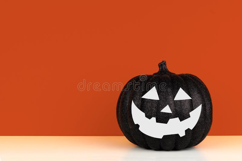 Black Halloween Jack o Lantern decoration on a shelf against an autumn orange background stock image