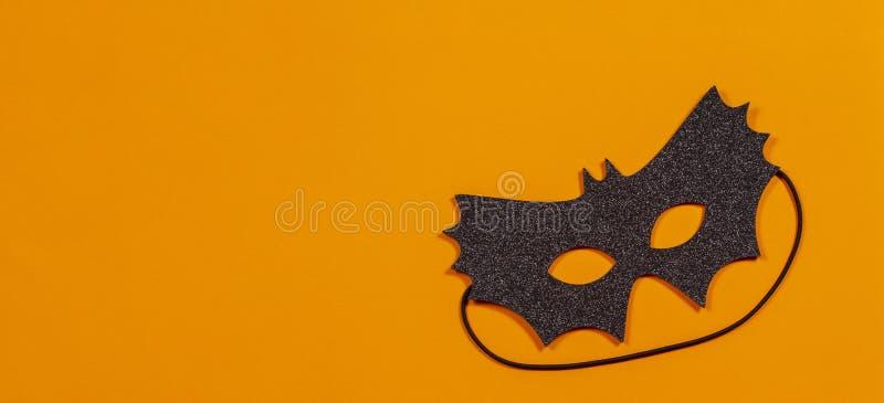 Black halloween mask on orange background.  royalty free stock photography