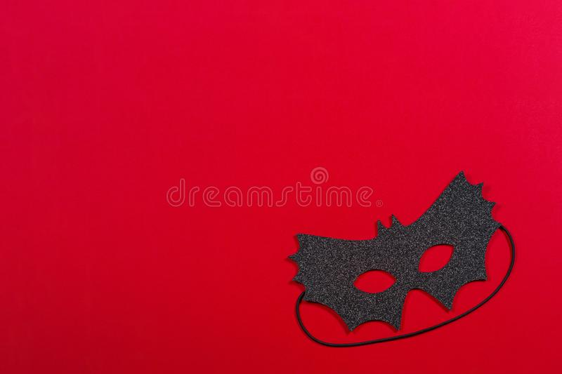 Black halloween mask on red background.  stock image