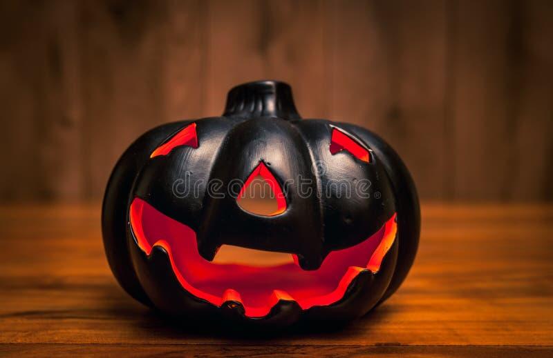 Black halowwen pumpkin on wooden background / Haloween background concept with jack-o-lantern.  stock photography