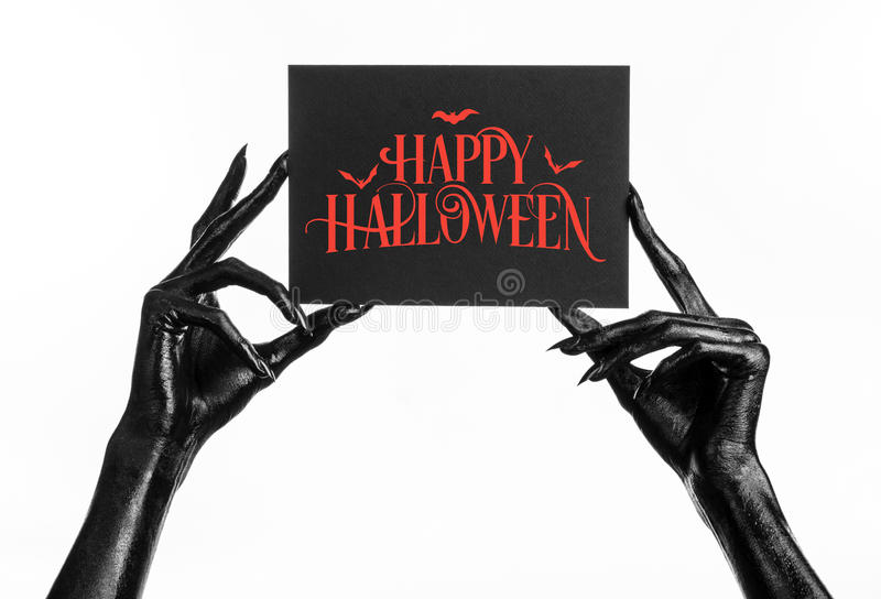 Black hand of death holding a paper card with the words Happy Halloween. Postcard and Happy Halloween theme: black hand of death holding a paper card with the stock photography