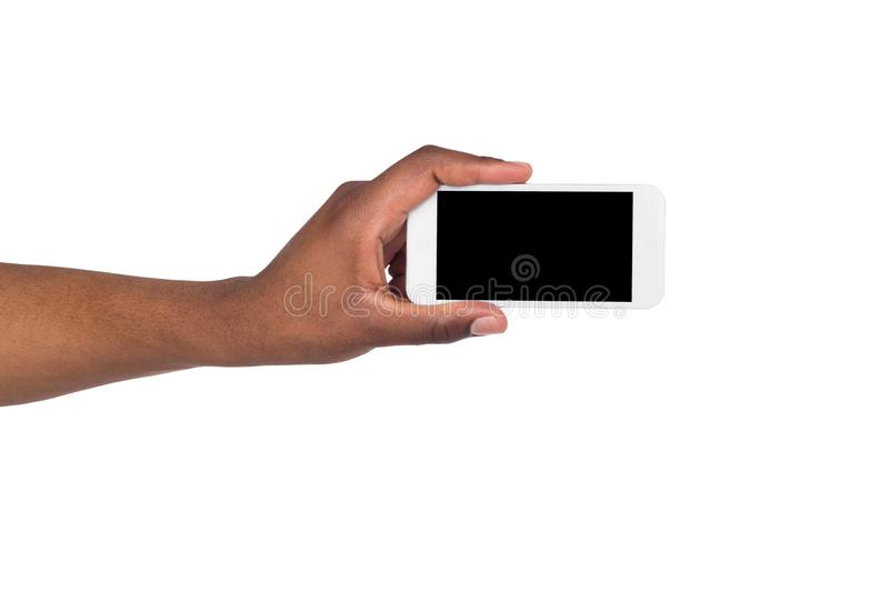 Black hand holding smartphone on isolated white background royalty free stock photos